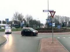 U rijdt op een rotonde en er komt een politieauto met zwaailichten achter u aan. Wat doet u?plaatje